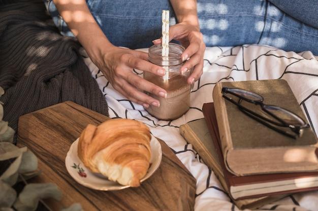 Mujer de cultivos con bebida cerca de libros y croissant