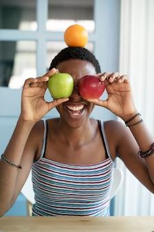 Mujer de descendencia africana con frutas en la cara