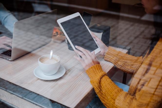 Mujer de la cosecha que usa la tableta que se sienta en café