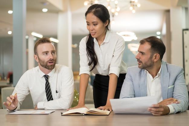 Mujer de negocios asiáticos trabajando con colegas en la oficina