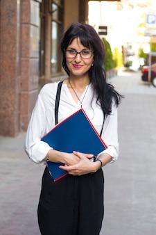 Mujer de negocios atractivo con papeles de trabajo en las manos en una calle de la ciudad