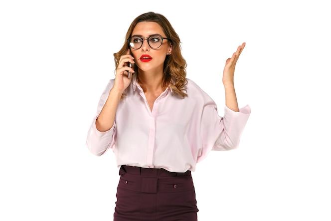 Mujer de negocios bonita joven hablando por el teléfono móvil, se ve confundido