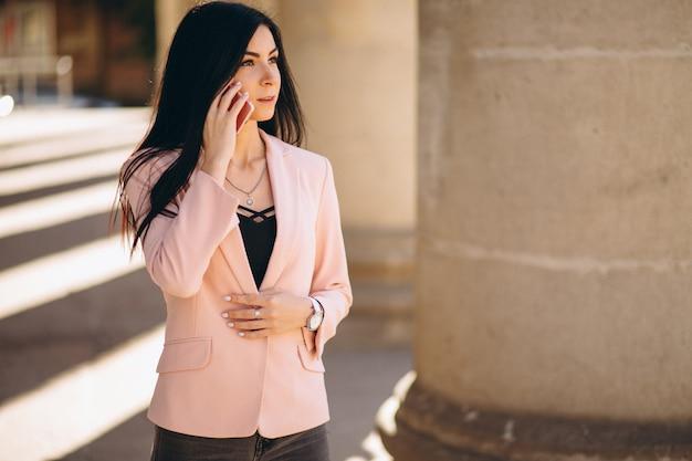 Mujer de negocios con chaqueta afuera en la ciudad