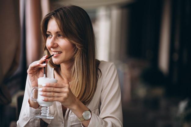 Mujer de negocios en un café bebiendo café con leche
