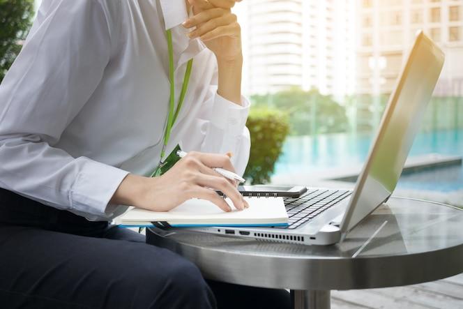 Mujer de negocios feliz que trabaja con la computadora portátil y el cuaderno al aire libre