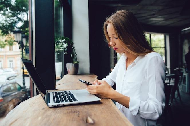Mujer de negocios joven que usa un teléfono móvil, mientras que se sienta para la tabla con la computadora portátil