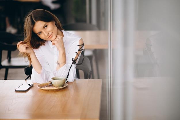 Mujer de negocios joven sentado en un café con café y teléfono