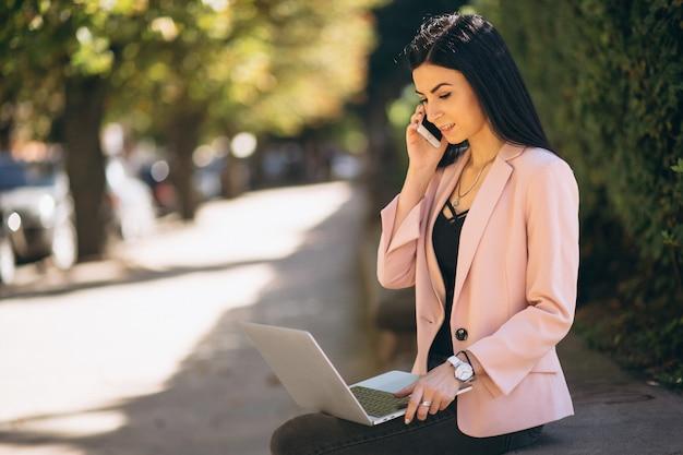 Mujer de negocios que trabaja en la computadora portátil afuera