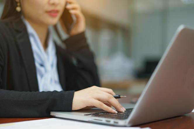 Mujer de negocios que trabaja en la oficina con la computadora portátil y documentos en su escritorio