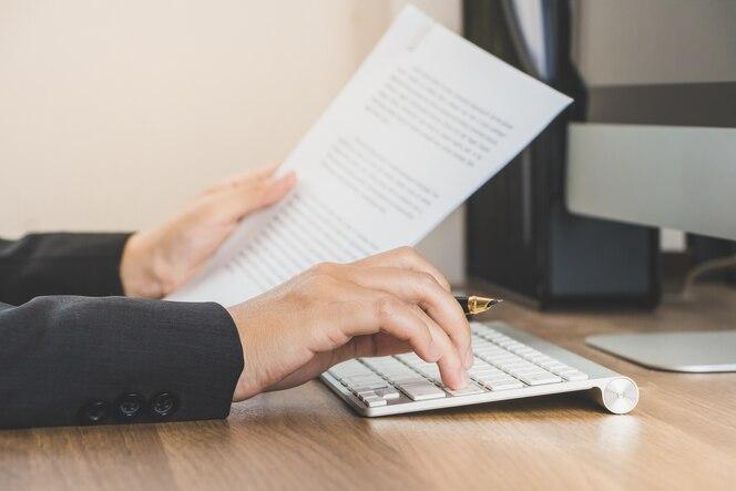Mujer de negocios que trabaja en la oficina con la computadora y documentos en su escritorio