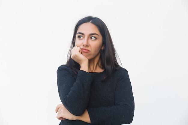Mujer decepcionada pensativa inclinando la barbilla en la mano