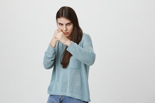 Mujer decidida seria de pie pose defensiva, boxeo