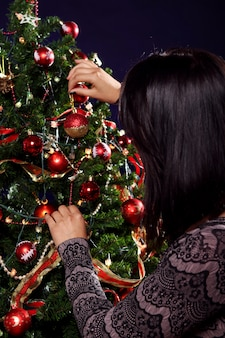 La mujer está decorando el árbol de navidad