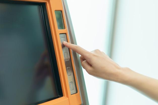 Mujer dedo presionando un botón atm