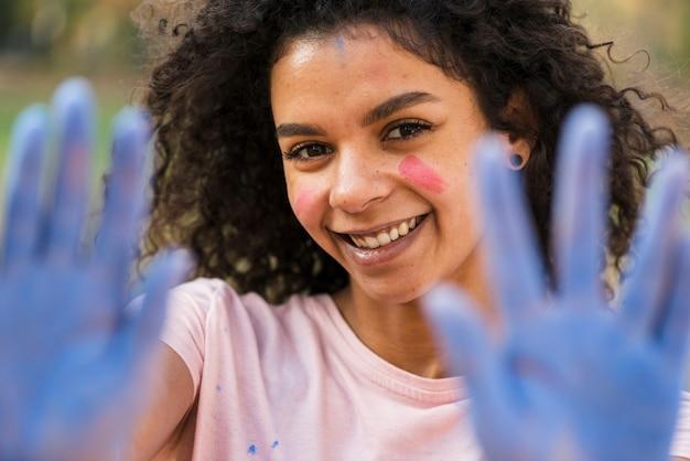 Mujer defocused que muestra las manos cubiertas azules