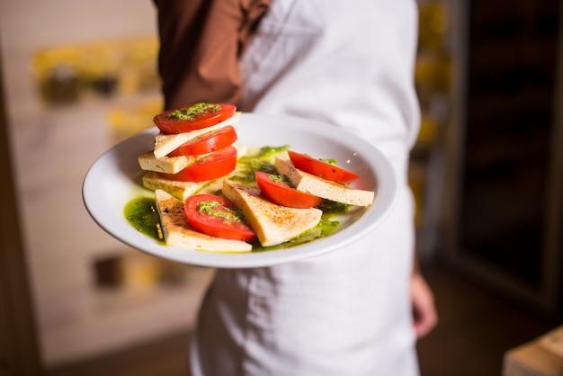 Mujer en un delantal blanco sosteniendo en la mano deliciosas comidas vegetarianas ensalada de tomate caprese con salsa de albahaca y queso en un plato blanco.