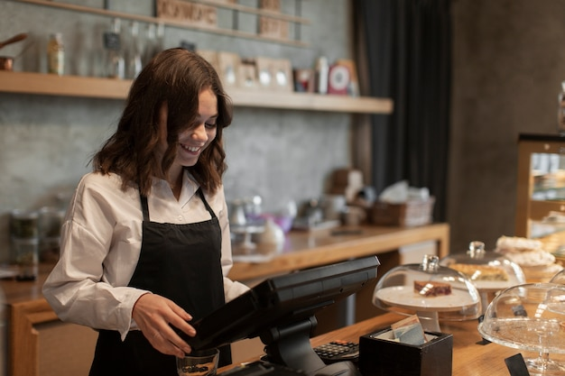 Mujer con delantal en caja registradora en cafetería