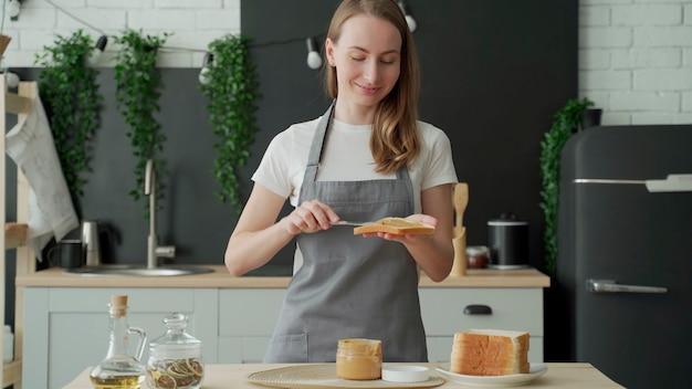 Una mujer se para en un delantal en la cocina y unta mantequilla de maní en una tostada