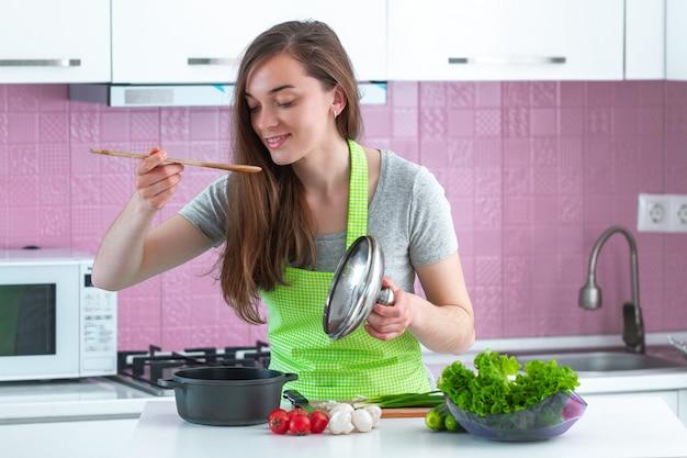 Mujer en delantal degustación de platos de verduras maduras en casa. comida limpia y nutrición adecuada. estilo de vida saludable, dieta. preparación de cocina para el almuerzo.