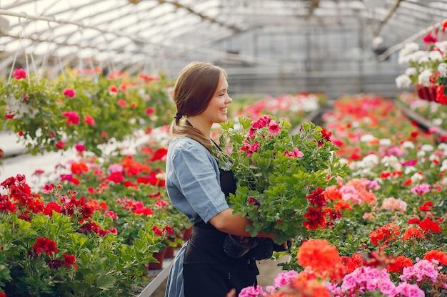 Mujer en un delantal negro trabajando en un invernadero