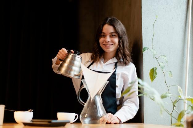 Mujer en delantal posando con cafetera