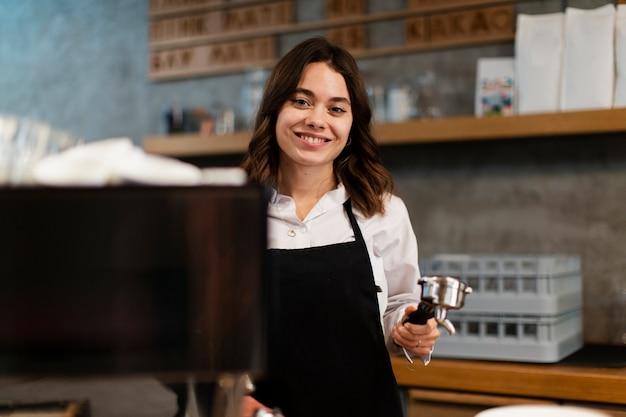 Mujer con delantal posando con componente de máquina de café