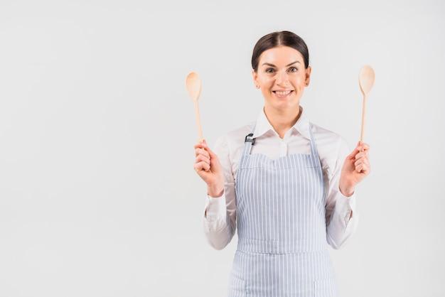 Mujer en delantal sonriendo y sosteniendo cucharas