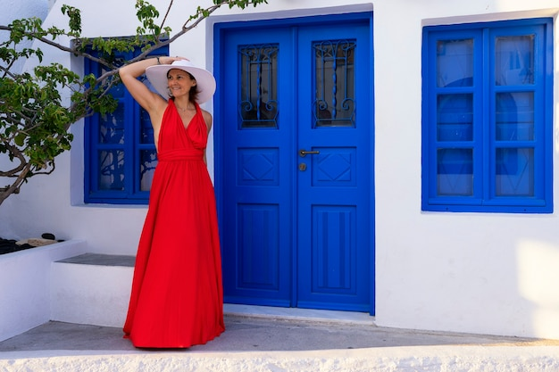 Mujer delante de la puerta azul en oia, santorini, grecia