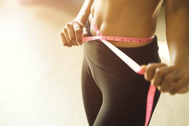 Mujer delgada atlética midiendo su cintura con cinta métrica