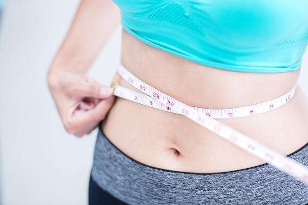 La mujer delgada del deporte mide su cintura con una cinta métrica