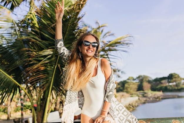 Mujer delgada disfrutando en un lugar exótico. señora bronceada alegre de pie cerca de palmeras y sonriendo.