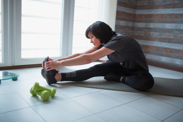 Mujer delgada en forma adulta tiene entrenamiento en casa. foto de modelo senior sentada en una estera de yoga y estirando hacia adelante hasta los dedos de los pies. cuida el bienestar del cuerpo.