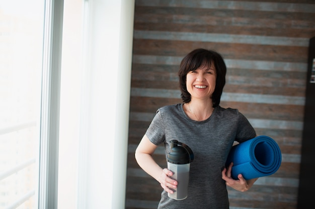 Mujer delgada en forma adulta tiene entrenamiento en casa. hembra mayor alegre positiva que mira en cámara y sonrisa. sosteniendo el batido de proteínas y la estera de yoga en las manos después del ejercicio. descansa y relajate.