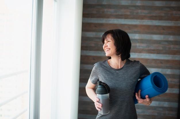 Mujer delgada en forma adulta tiene entrenamiento en casa. persona de sexo femenino mayor positiva alegre que sonríe y que mira la ventana. mujer después de hacer ejercicio beber batido de proteínas y sostener estera de yoga.