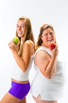 Mujer delgada y gorda con manzana en la mano