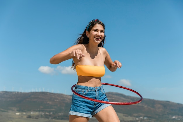 Mujer delgada joven que da vuelta al aro del hula alrededor de la cintura