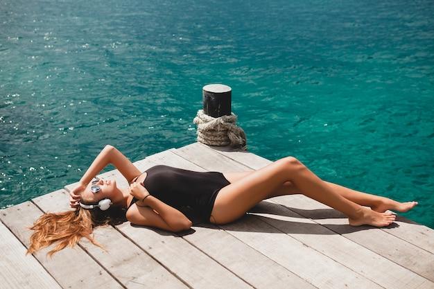 Mujer delgada joven tendido en el muelle, mar mediterráneo, agua azul, piel bronceada y soleada, escuchar música, auriculares, traje de baño negro, cuerpo sexy, tomar el sol, vacaciones tropicales, relajado, gafas de sol