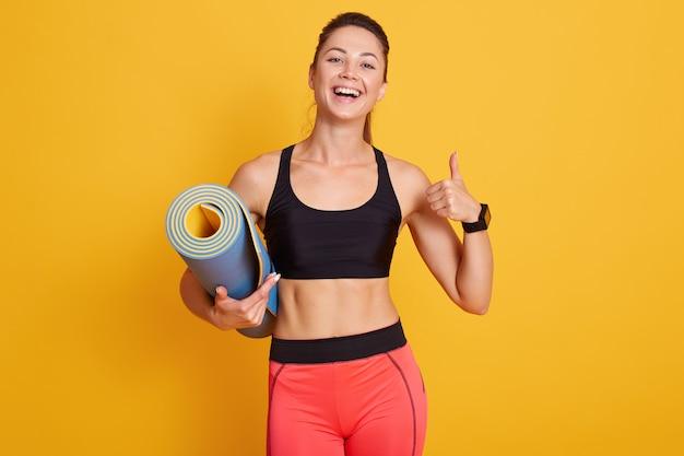 Mujer delgada lista para entrenar con colchoneta de yoga y pulgares arriba