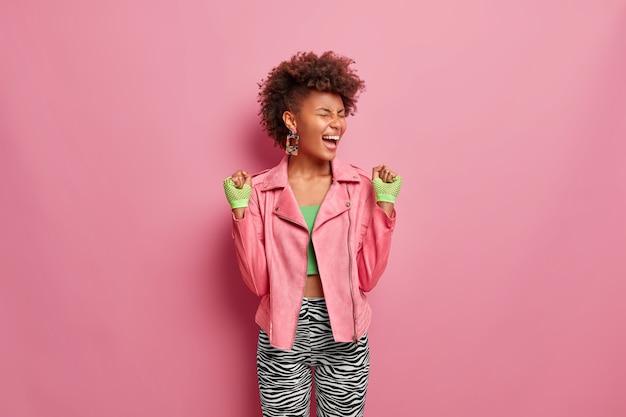 Mujer delgada llena de alegría tiene el pelo afro aprieta los puños con alegría, se siente muy feliz y afortunada después de entrenar en el gimnasio