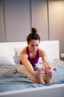 Mujer delgada de mediana edad sana que estira el ejercicio de yoga mientras se sienta hacia adelante en la cama mientras sus manos sostienen los pies.