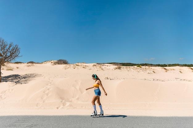 Mujer delgada patinando en el camino de arena