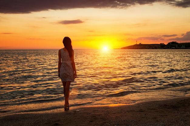 Una mujer delgada se para en la playa observando la puesta de sol, la puesta de sol va en el horizonte hacia el mar
