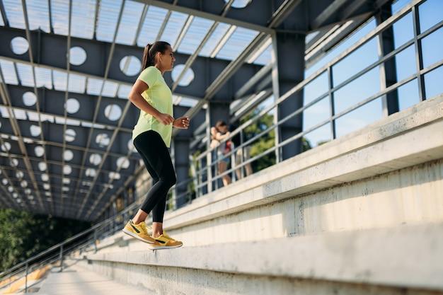 Mujer delgada positiva en ropa deportiva subiendo escaleras en el estadio de la ciudad.