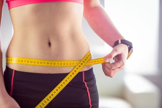 Mujer delgada que mide la cintura con cinta métrica