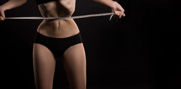 Mujer delgada que mide su cintura con una cinta métrica después de una dieta sobre fondo oscuro