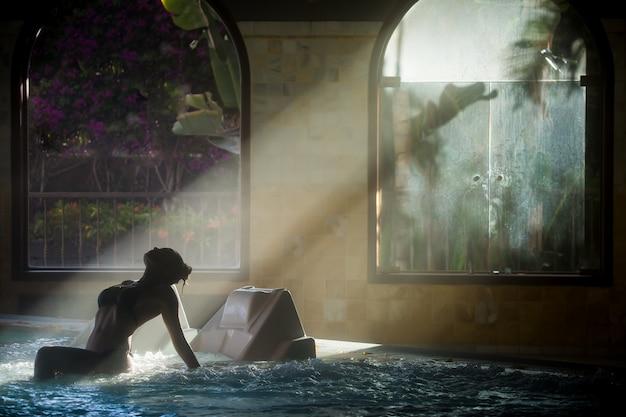 Mujer delgada relajándose en el agua del jacuzzi