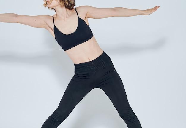 Una mujer delgada en ropa deportiva se dedica a la aptitud sobre un fondo claro