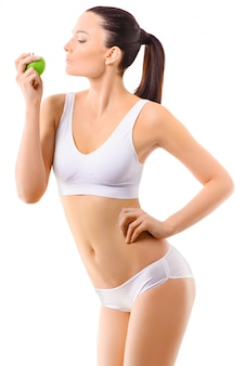 Mujer delgada en ropa interior blanca con manzana verde en sus manos sobre fondo aislado