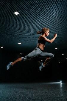 Mujer delgada está saltando activamente alto en ropa deportiva sobre un fondo negro del gimnasio dinámico mo ...