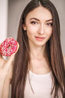 Mujer delgada sostenga en la mano rosquilla rosa